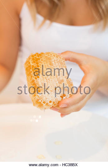 Hand of young woman holding honeycomb. - Stock Image