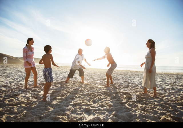 Multi-generation family playing volleyball on beach - Stock Image