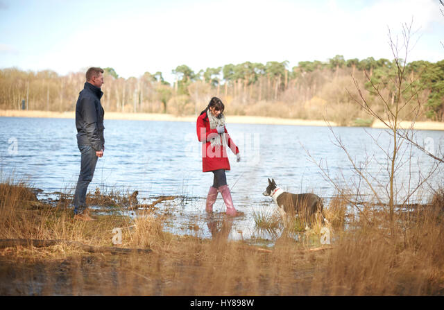 A young couple on a walk in the woods by a lake - Stock Image