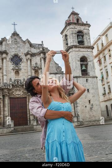 Young couple taking selfie with smartphone in the Plaza de la Cathedral of Havana, Cuba - Stock Image