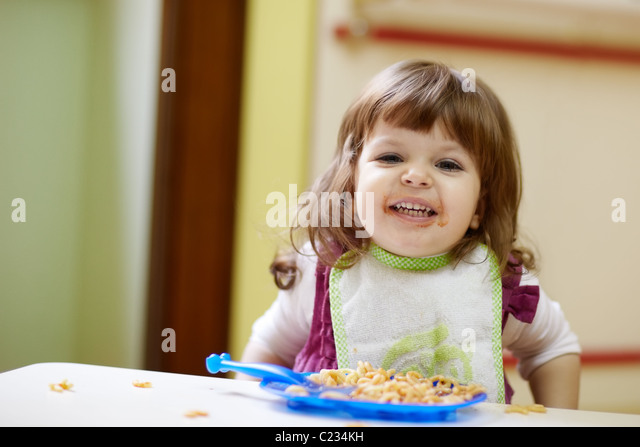 caucasian female preschooler eating pasta and smiling at camera. Horizontal shape, waist up, front view - Stock Image