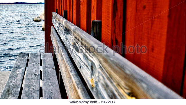 Swedish red wall and sea,partial clarity. Wooden bench on jetty. - Stock Image