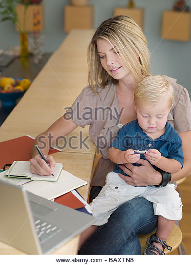 Mother working and holding son on lap - Stock Image