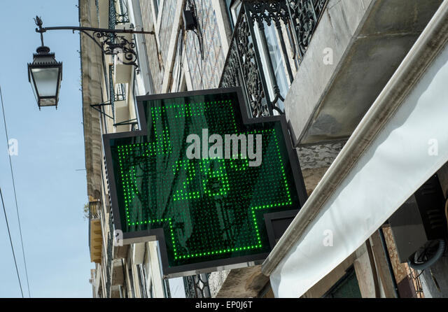 Illuminated green LED sign outside a pharmacy showing the temperature of 28 degrees centigrade - Stock Image