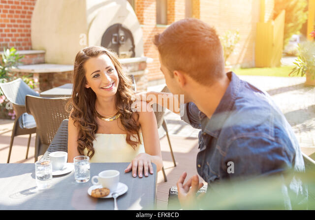 Young couple talking on the terrace of the restaurant, while eating - Stock-Bilder