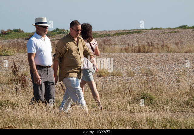 A woman and two men walking alongside Aldeburgh's pebbly beach - Stock Image