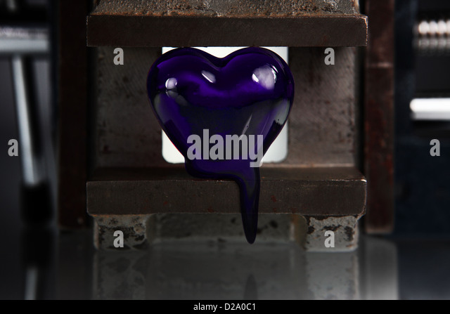 a purple blue heart that melts between the jaws of a vice or press. Low key. - Stock Image