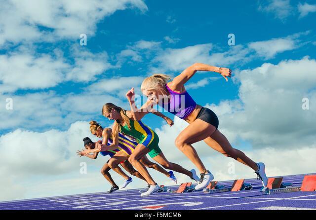Four female athletes on athletics track, leaving starting blocks - Stock-Bilder