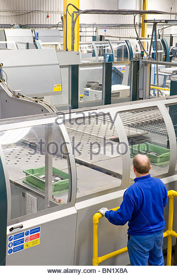 Worker watching machinery in factory that manufactures aluminium light fittings - Stock Image