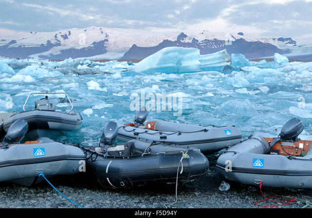 Dinghies, icebergs and snow-covered mountains, Jokulsarlon Glacier Lagoon,  Vatnajokull National Park, Iceland - Stock-Bilder