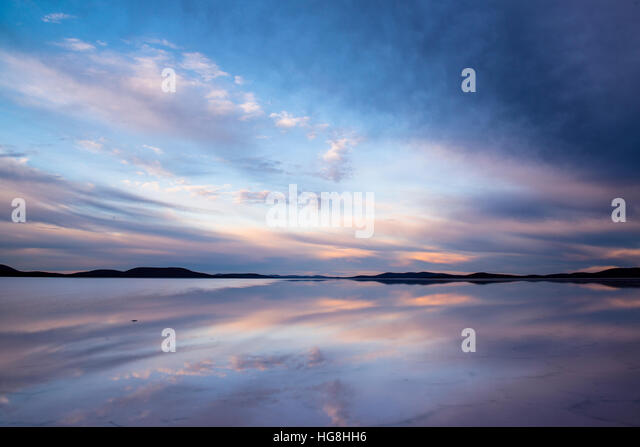 sunset sky and clouds reflect off of still water lake - Stock Image