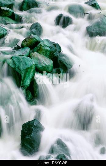 Water rushing over green rocks, Irian Jaya, New Guinea, Indonesia - Stock Image