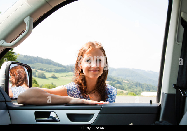 portrait of young woman looking through car window - Stock Image