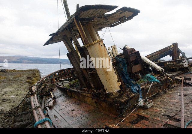 Wrecked fishing boats beached on shore at Salen, Isle of Mull. - Stock Image