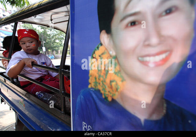A boy looks at an election poster of Aung San Suu Kyi in Yangon, 30 March 2012.  A wave of  reforms in politics, - Stock-Bilder