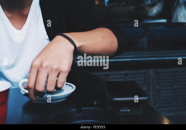 Midsection Of Man Having Coffee At Restaurant - Stock Image