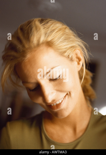 Woman, head down, smiling, close-up, portrait. - Stock Image