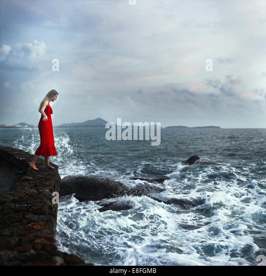 Woman standing on edge of cliffs, Koh Samui, Thailand - Stock Image