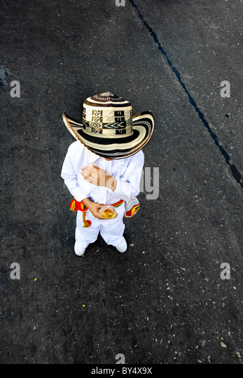 A Colombian boy, wearing a traditional Vueltiao hat, walks alone during the Carnival in Barranquilla, Colombia. - Stock Image