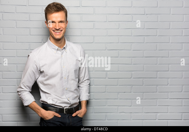 Male studio happy grey background looking camera - Stock Image