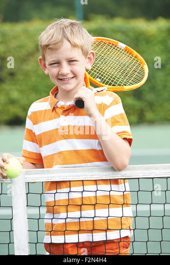 Portrait Of Boy Playing Tennis Standing Next To Net - Stock Image