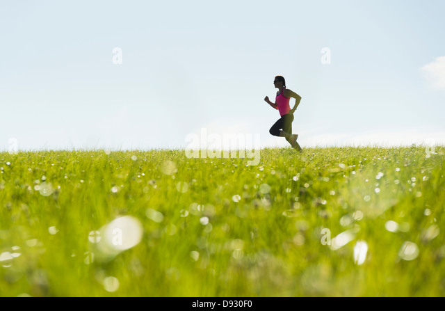 Woman jogging in meadow - Stock Image