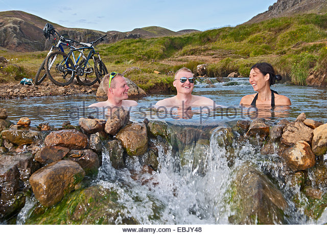 Low angle view of three mountain bikers bathing in hot river, Reykjadalur valley, South West Iceland - Stock Image