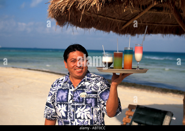 MEXICO Waiter on the beach with colorful drinks - Stock Image