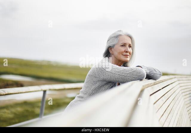 Serene senior woman leaning on boardwalk ledge - Stock Image
