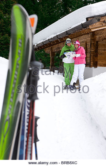 Couple standing in snow near lodge with skis looking at mail - Stock Image