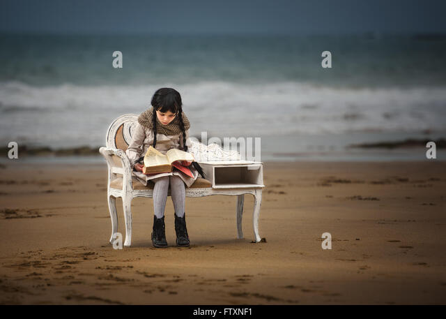 Girl reading a book on the beach - Stock Image