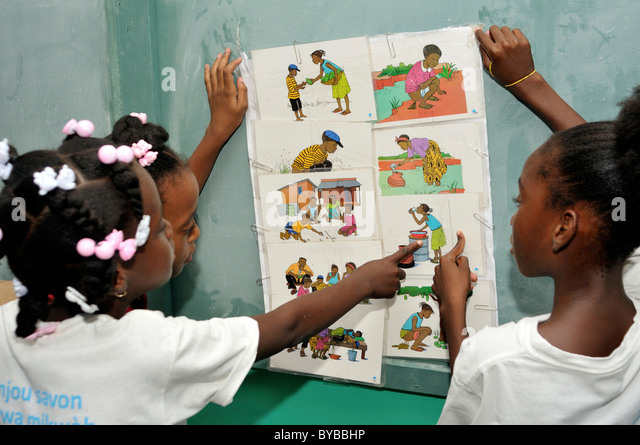 Children discussing scenes from everyday life concerning hygiene with the help of pictures, hygiene education campaign - Stock-Bilder