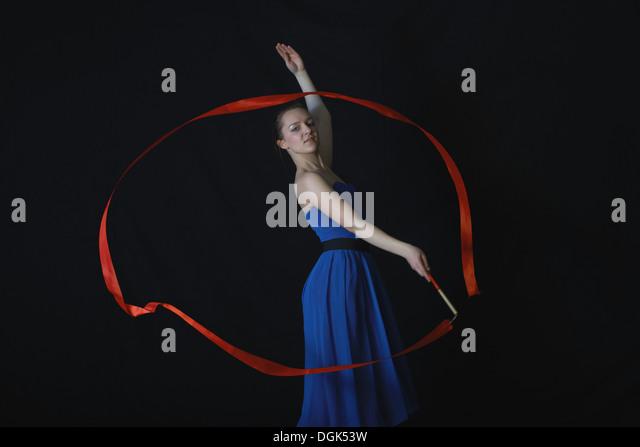 Dancer with ribbon on black background - Stock-Bilder