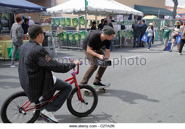 Miami Florida Little Havana Calle Ocho Street Festival Hispanic teen boy male bicycle skateboard video camera - Stock Image