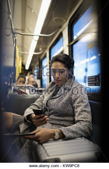 Businesswoman commuter with suitcase texting with smart phone on bus - Stock Image