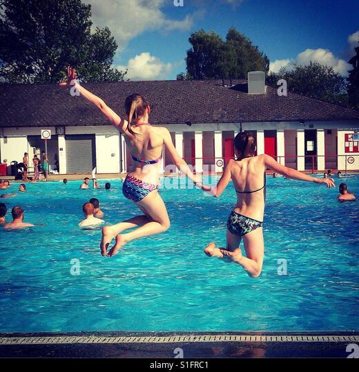 Two girls jumping into swimming pool - Stock-Bilder