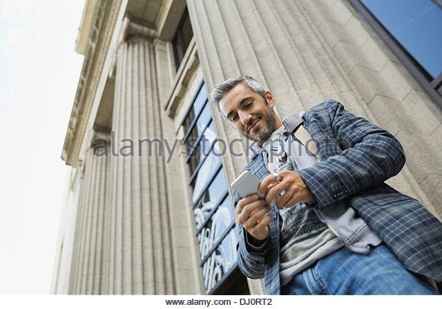 Low angle view of man using smart phone outdoors - Stock Image