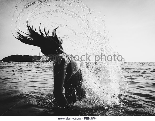 Woman Flipping Hair In Water - Stock Image