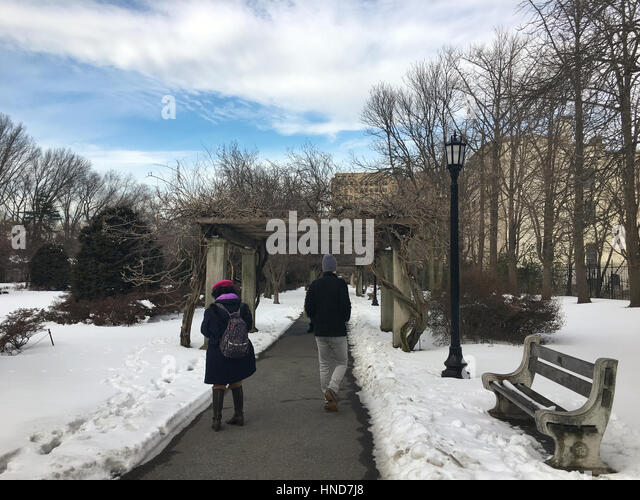 Tourists walking down a path at the Brooklyn Botanic Gardens after a Winter snowfall. - Stock Image