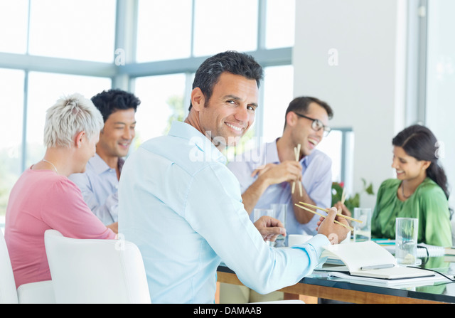 Businessman smiling in lunch meeting - Stock Image
