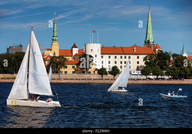 The boat on the river from the castle President of Latvia on the waterfront and city skyline Riga churches with - Stock Image