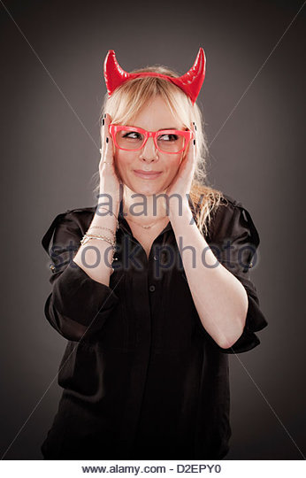Lauren Crace wearing red glasses and devil horns, studio portrait - Stock-Bilder