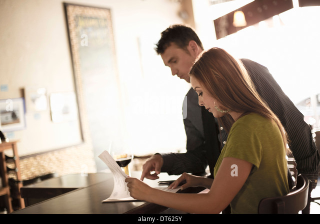 Business partners looking at paperwork in a wine bar - Stock-Bilder