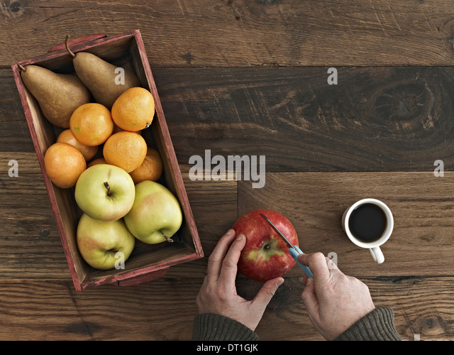 A wooden table top with variety of wood A box of fresh fruits pears and oranges A person chopping an apple - Stock Image