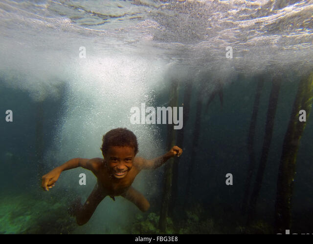 Boy underwater after jumping off jetty, Gam Island, Raja Ampat, West Papua, Indonesia - Stock Image