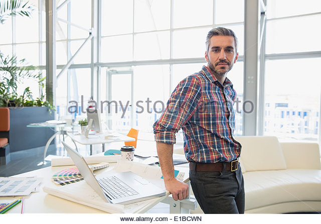 Portrait of creative businessman in office - Stock Image