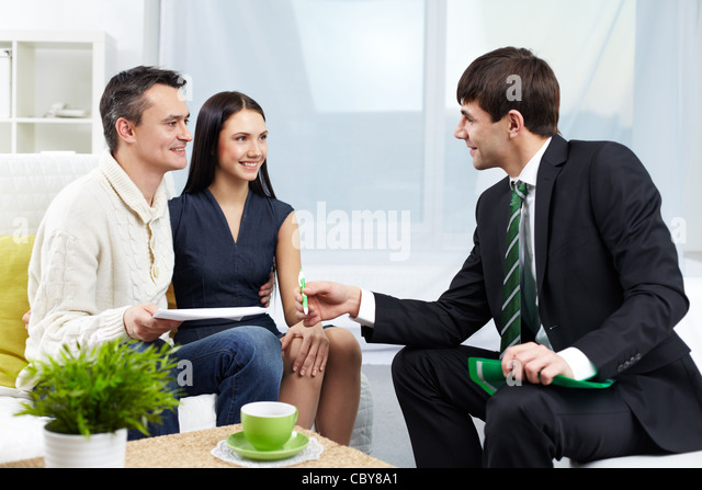 Portrait of modern couple looking at manager while discussing agreement - Stock Image