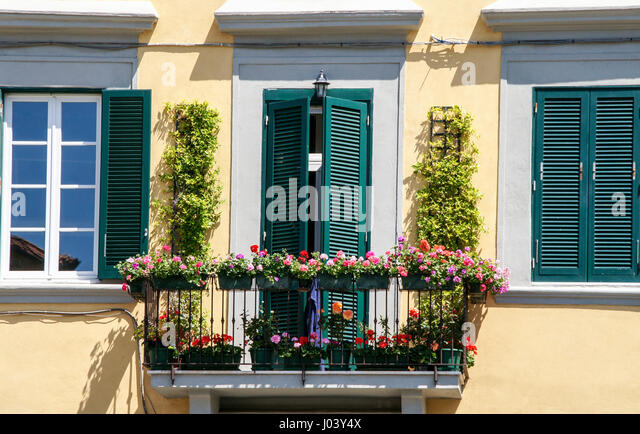 A beautiful flower decorated balcony and windows on a house in Livorno, Italy. - Stock Image