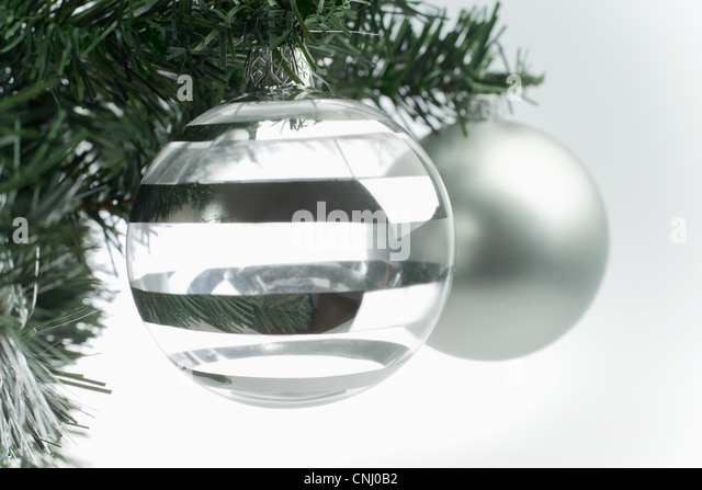 Silver christmas baubles on tree - Stock Image