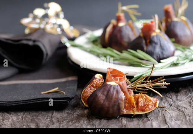Open fig, in the background a plate with figs and rosemary - Stock Image
